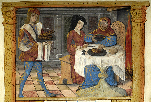 Servant, wearing hat, supporting with both hands platter on which is bird, approaches draped round table.